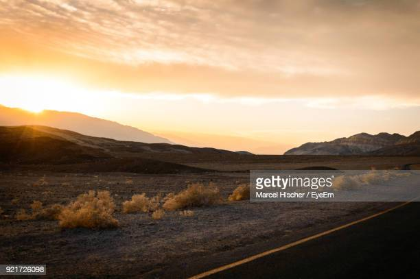 scenic view of landscape against sky during sunset - death valley photos et images de collection
