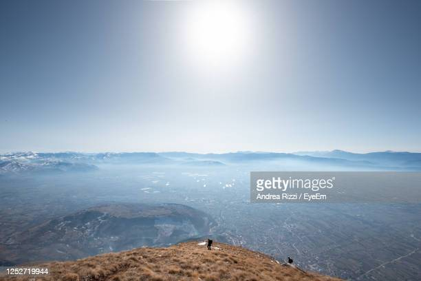 scenic view of landscape against sky on sunny day - andrea rizzi stockfoto's en -beelden
