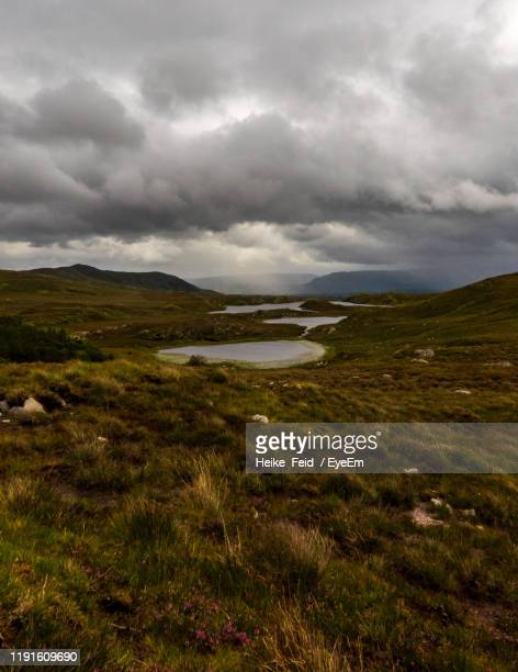 scenic view of landscape against sky - storm cloud stock pictures, royalty-free photos & images