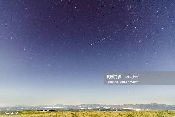 scenic view of landscape against star field at dawn - north star stock photos and pictures