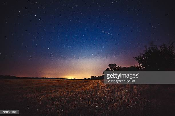 Scenic View Of Landscape Against Star Field In Sky At Dusk