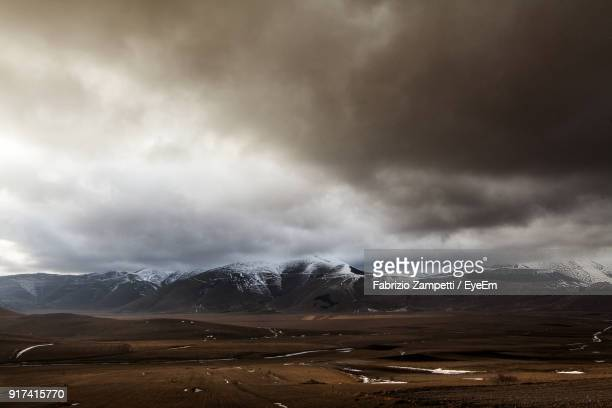 scenic view of landscape against storm clouds - fabrizio zampetti foto e immagini stock