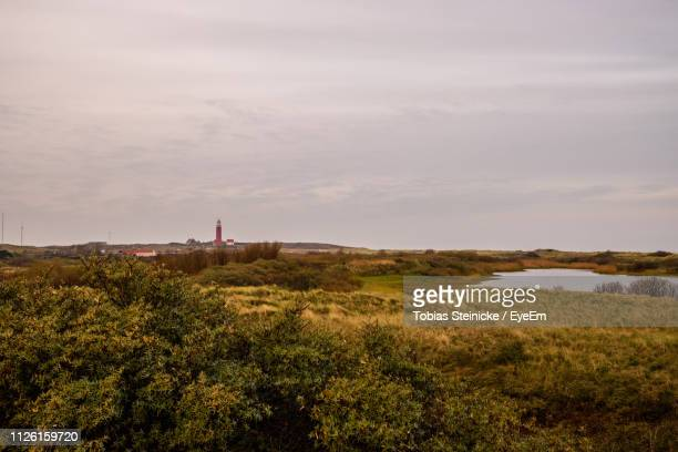 scenic view of landscape and lighthouse against sky - noord holland stockfoto's en -beelden