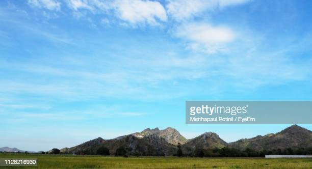 scenic view of landscape and mountains against blue sky - metthapaul stock photos and pictures