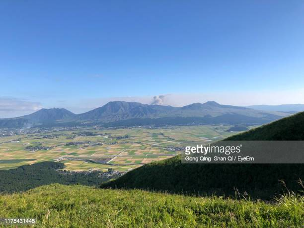 scenic view of landscape and mountains against blue sky - kumamoto prefecture stock pictures, royalty-free photos & images