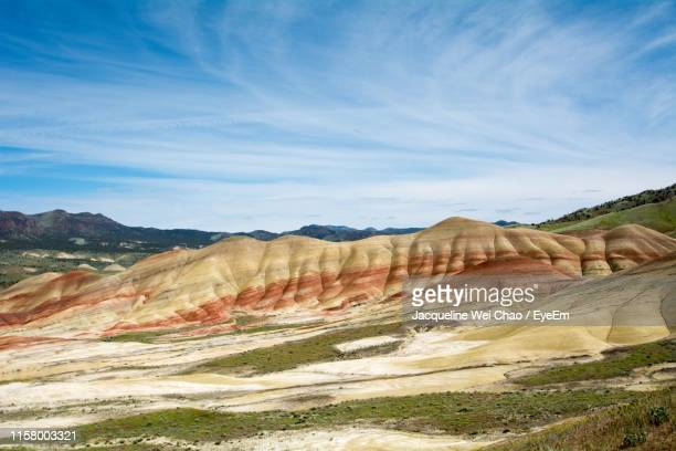 scenic view of landscape and mountains against cloudy sky - john day fossil beds national park stock pictures, royalty-free photos & images
