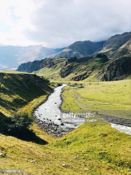 scenic view of landscape and mountains against sky - georgia stock-fotos und bilder
