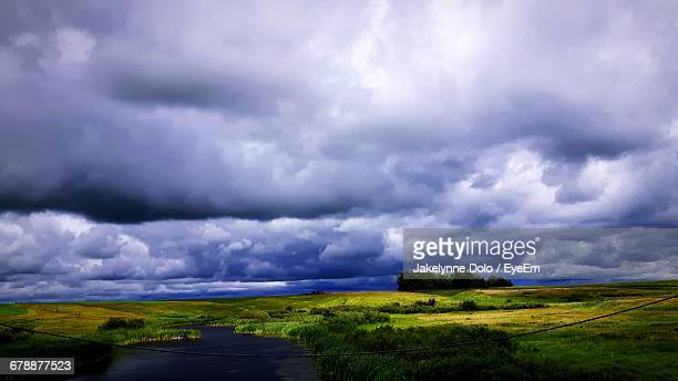 Scenic View Of Landscape And River Against Cloudy Sky