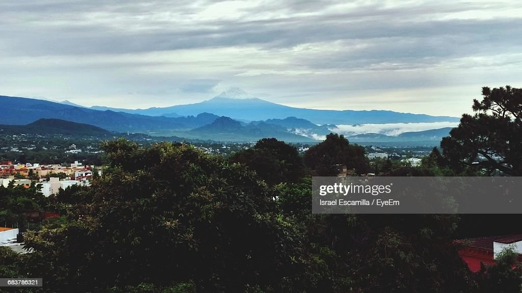 Scenic View Of Landscape By Mountains Against Cloudy Sky : Foto de stock