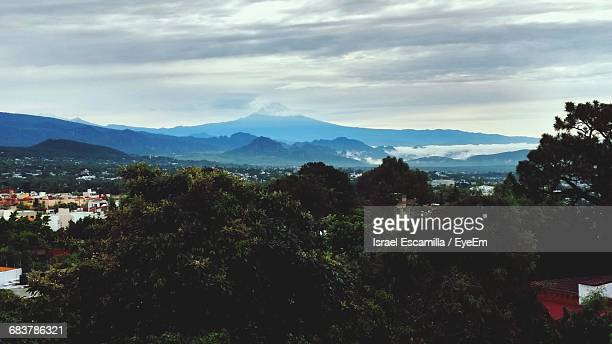 Scenic View Of Landscape By Mountains Against Cloudy Sky