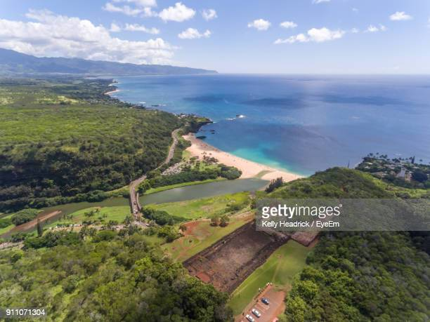 scenic view of landscape by sea against sky - waimea bay stock photos and pictures