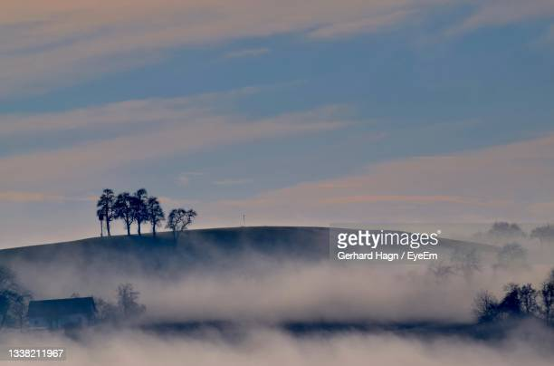 scenic view of landscape with fog against sky during sunset - gerhard hagn stock-fotos und bilder