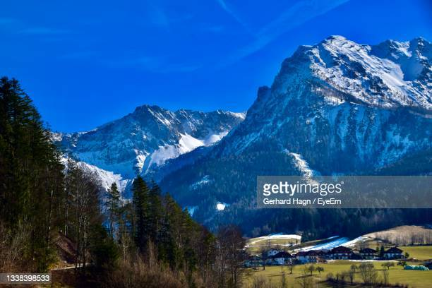 scenic view of landscape with houses and snowcapped mountains against blue sky - gerhard hagn stock-fotos und bilder