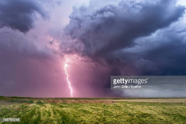 scenic view of lightning over field - nube temporalesca foto e immagini stock