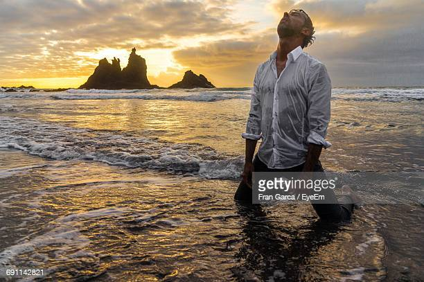 scenic view of man in sea against cloudy sky at sunset - wet shirt stock photos and pictures