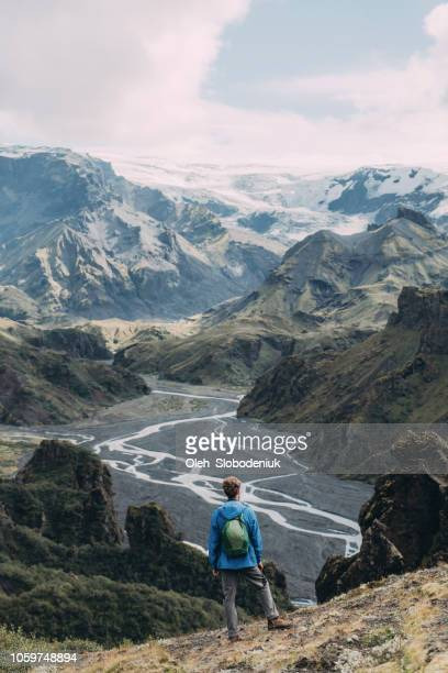 scenic view of man looking at thórsmörk river valley - valley stock pictures, royalty-free photos & images