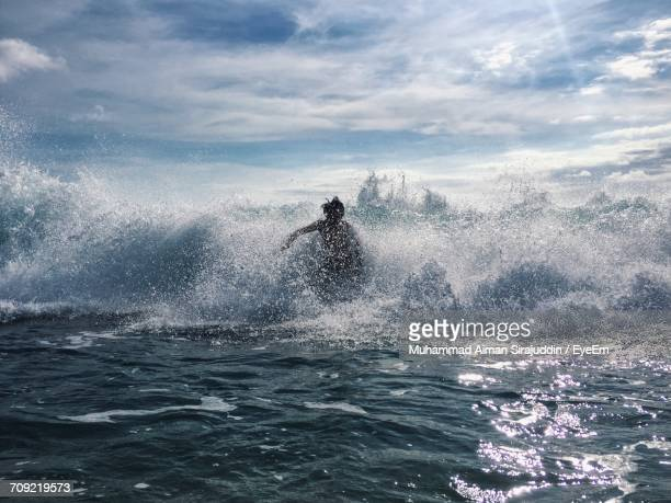 Scenic View Of Man Surfing And Splashing In Sea Against Sky