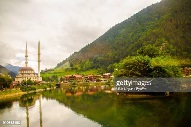 scenic view of mosque by lake and mountain against sky - trabzon stock photos and pictures