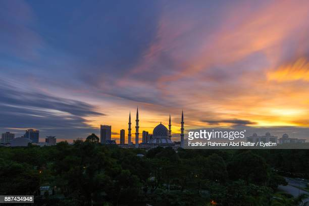 scenic view of mosque by trees against cloudy sky during sunset - shah alam stock photos and pictures