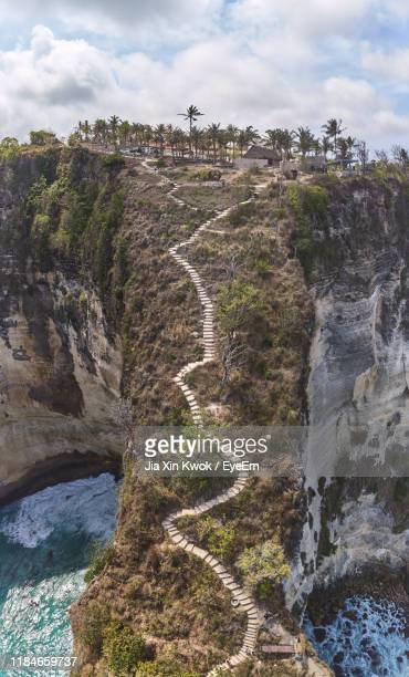 scenic view of mountain against cloudy sky - nusa penida stock pictures, royalty-free photos & images