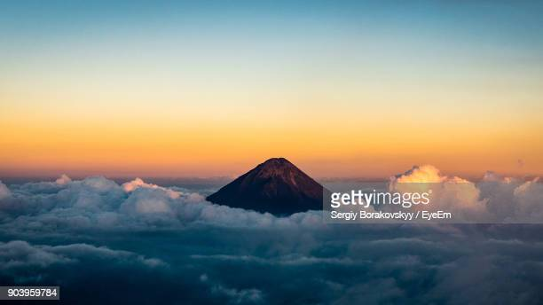 Scenic View Of Mountain Amidst Clouds During Sunset