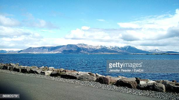 Scenic View Of Mountain And Sea Against Cloudy Sky