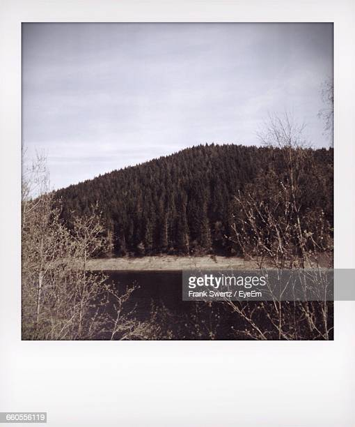 scenic view of mountain by river against sky - frank swertz stockfoto's en -beelden