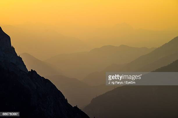 scenic view of mountain range in foggy weather during sunset - berchtesgaden alps stock photos and pictures