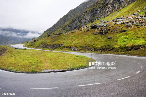 scenic view of mountain road against sky - hairpin stock pictures, royalty-free photos & images