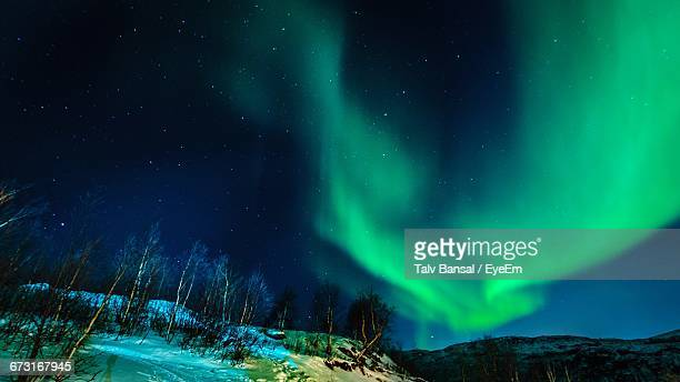 Scenic View Of Mountains Against Aurora Borealis In Sky At Night