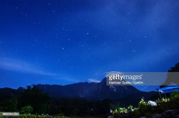 scenic view of mountains against blue sky at night - kota kinabalu stock pictures, royalty-free photos & images