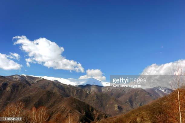 scenic view of mountains against blue sky - alex olariu stock photos and pictures