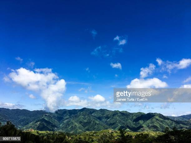 scenic view of mountains against blue sky - davao city stock photos and pictures