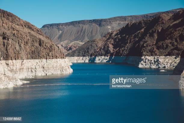 scenic view of mountains against clear blue sky - bortes foto e immagini stock