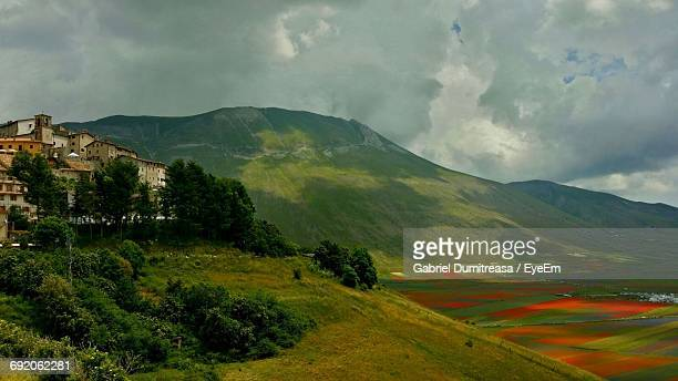 scenic view of mountains against cloudy sky at castelluccio - カステッルッチョ ストックフォトと画像