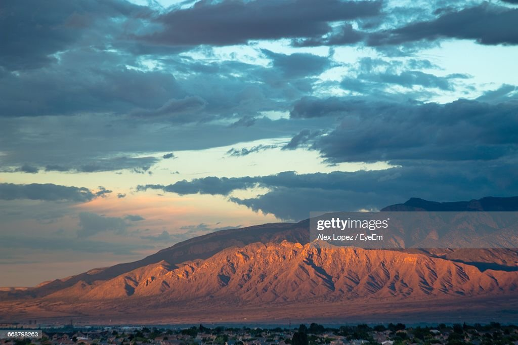 Scenic View Of Mountains Against Cloudy Sky During Sunset : Stock Photo
