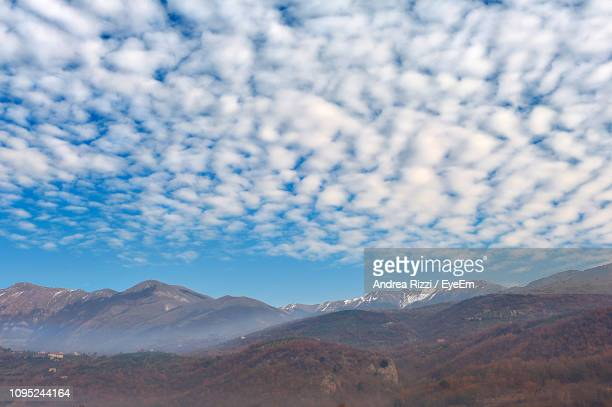scenic view of mountains against cloudy sky - andrea rizzi stock pictures, royalty-free photos & images