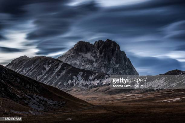 scenic view of mountains against cloudy sky - andrea rizzi stockfoto's en -beelden