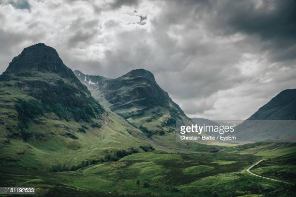 scenic view of mountains against cloudy sky - glencoe scotland stock pictures, royalty-free photos & images