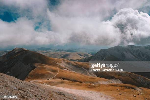 scenic view of mountains against cloudy sky - fabrizio zampetti foto e immagini stock
