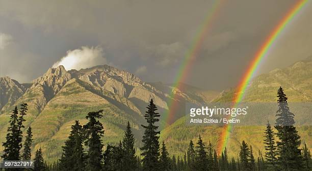 Scenic View Of Mountains Against Double Rainbow