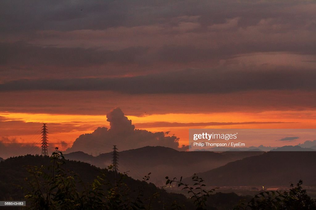 Scenic View Of Mountains Against Dramatic Sky During Sunset : Stock Photo