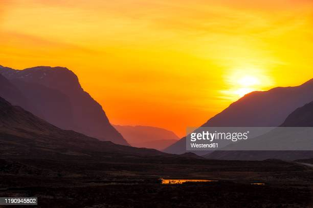 scenic view of mountains against orange sky at glencoe, highlands, scotland, uk - sunset stock pictures, royalty-free photos & images