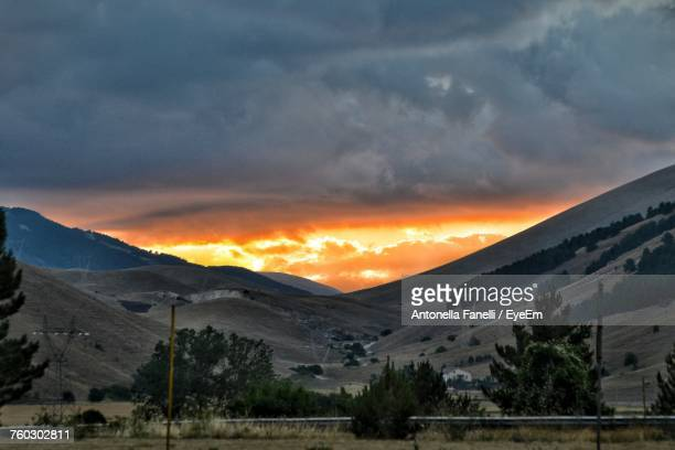 scenic view of mountains against orange sky - antonella stock photos and pictures