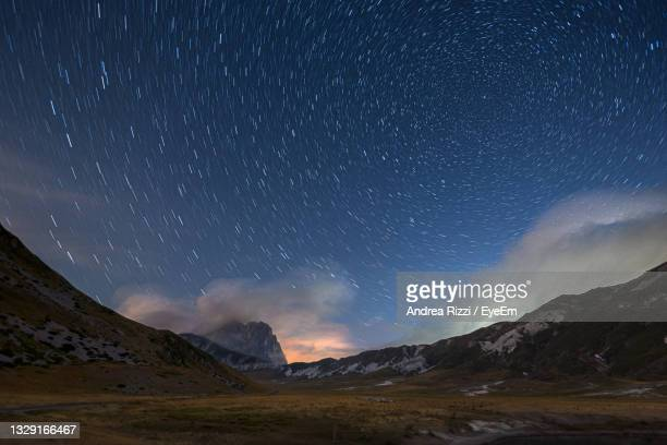 scenic view of mountains against sky at night, campo imperatore - andrea rizzi stock pictures, royalty-free photos & images