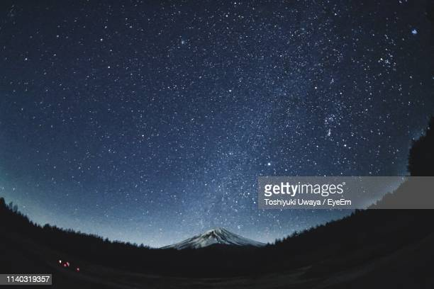 scenic view of mountains against sky at night - stars sky ストックフォトと画像
