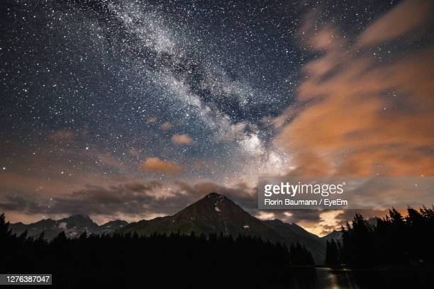 scenic view of mountains against sky at night - switzerland stock pictures, royalty-free photos & images