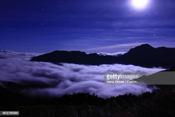 scenic view of mountains against sky at night - 月の光 ストックフォトと画像