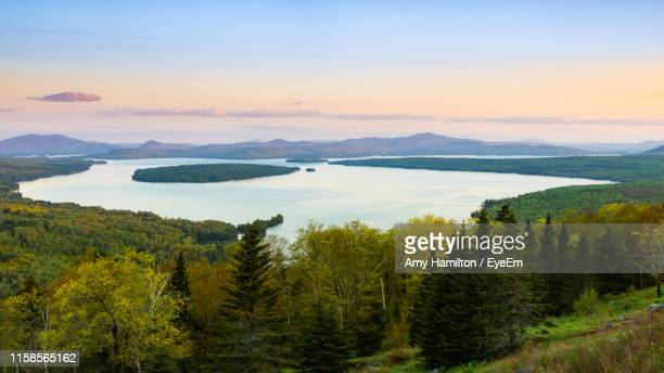 scenic view of mountains against sky during sunset - mooselookmeguntic lake stock photos and pictures