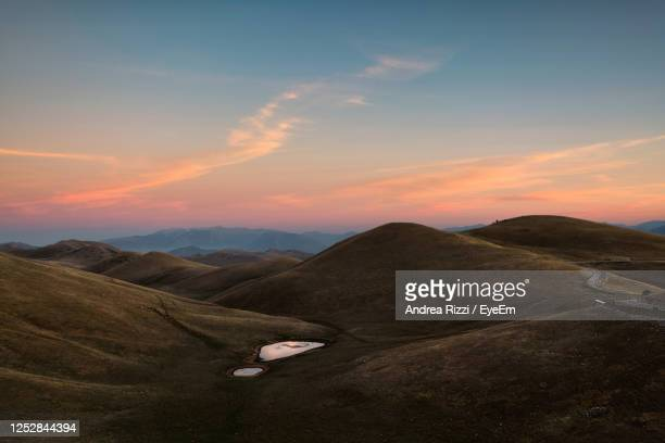 scenic view of mountains against sky during sunset - andrea rizzi stockfoto's en -beelden